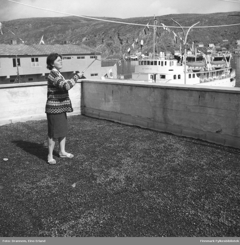 Maija, ukjent etternavn, spiller badminton på verandataket til Tollboden. I bakgrunnen ved kai ligger båten Brand IV. Bak den kan man også se Vesterålskes godsbåt M/S Vardø på vei ut havna.