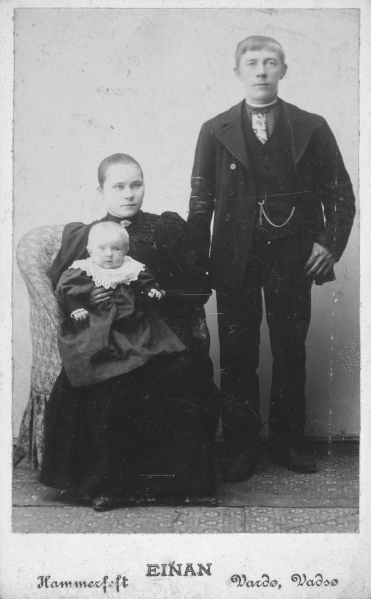 Visittkortportrett av et ungt par. Kvinne sitter med et spedbarn i fanget og mannen står vid siden av dem.