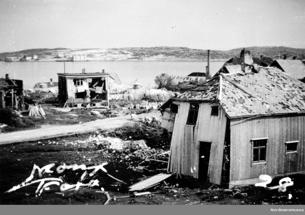 """Ødelagt hus etter sprengbomben på Dahle ved Kristiansund, 28. april 1940. I forgrunnen skimter en tomten og området hvor 4 mennesker ble drept. De drepte var Peder Gaupseth, Kristian Gundersen, moren i Ohrvikhuset Olga Ohrvik og sønnen Asbjørn Ohrvik.                                                                Det ødelagte huset i front tilhørte familien John Sund. Til venstre for Sunds hus ses huset til familien Melvin Ingebrigtsen og helt til venstre ses en bit av det ødelagte Hollekimhuset.       Mellom Hollekimhuset og Ingebrigtsenhuset ses taket på huset til familien John Bakken, og til høyre for Ingebrigtsenhuset ses taket på huset til familien Kristian Stabben. Bak Ingebrigtsenhuset ses klippfiskbergene, nedre Amundbergene, med klippfiskla. Over taket, og bak skorsteinen, på Sundhuset, ses taket på huset til familien Peder Moen og til høyre for Moenhuset ses taket på huset til familien Liabø. Bak, og over taket på Moens og Liabøs hus, ses """"Murgården"""", Storviks mek. Verksteds leilighetshus, og til venstre for det ses kobberslagerverkstedsbygget med den høye skorsteinspipen. Daleveien ses som en grå stripe på bildet.                                                       På veien opp til Persløkka er det satt opp en minnetavle med navn på drepte etter bombingen.      I bakgrunnen ses Skorpa og Visnesbrygga.                                                                                                                    Bildet er fra 1940. (Petter Storvik) -- Foto fra utbombede husruiner på Dale, Nordlandet i Kristiansund, med Skropa i bakgrunnen. Bildet er stemplet Monge foto, og datert til april 1940, da trolig den 28 etter påført nummer - det vil si samme dag som byen ble bombet for første gang. Fra Nordmøre museums fotosamlinger."""