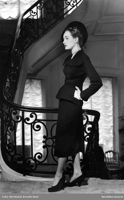 """Modell i La Ligne Corolle, """"The New Look"""". Modellen står i trapphuset hos modehuset Dior på Avenue Montaigne i Paris."""