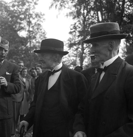 Foto av två äldre män i kostym och hatt, vid Christina Nilsson-jubileet 1943. Vederslöv.