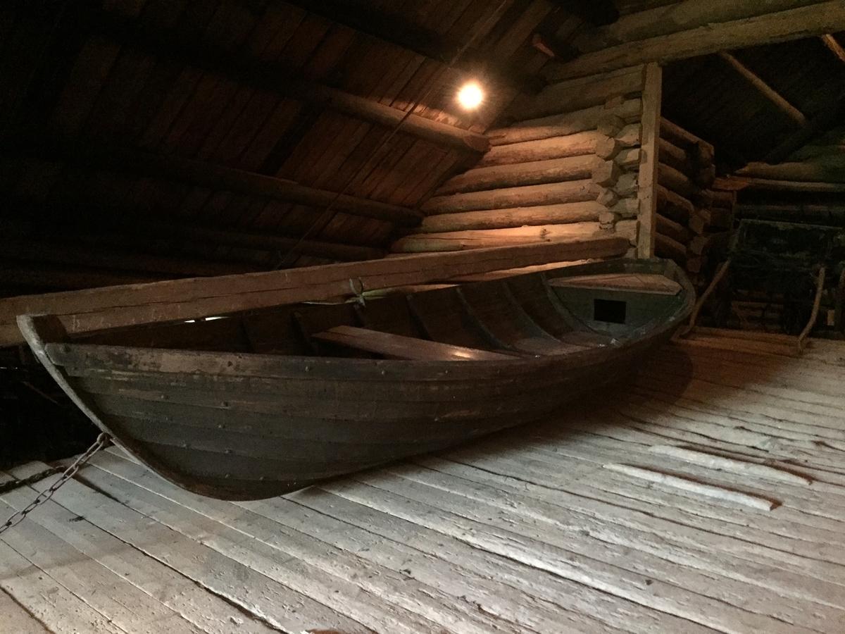 """Bred, klinkbygd båt beregnet for tømmerfløting. 7 spanter, 12 bordganger, esing på øverste bordgang.  2 åregafler. """"Innreiinga"""" består av en """"splitt"""" - et trkantet bord - i hver ende, 6 """"flak"""" (bunnbrett) og en """"fjøl"""" (tofte)."""