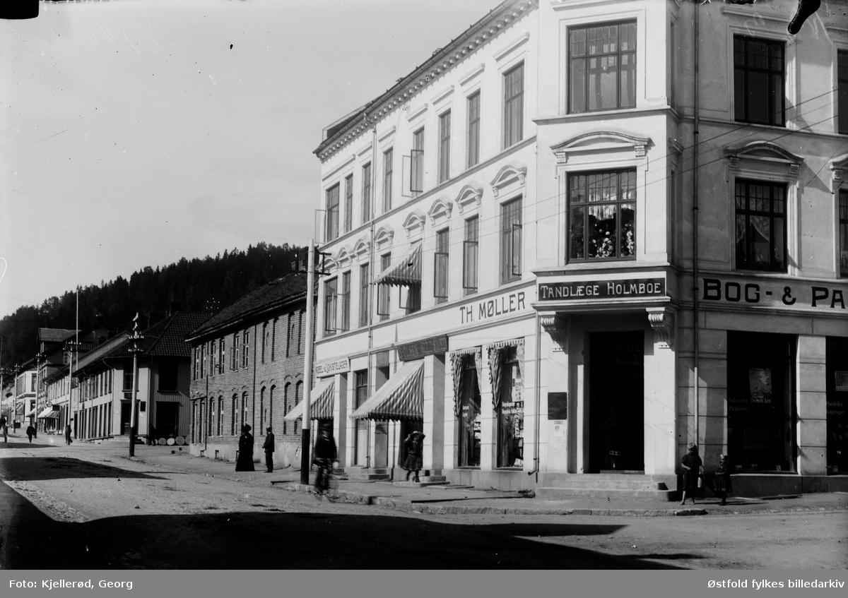 Gateparti fra Storgata i Gjøvik, Møbel. og ligkistelager. Gullsmed H. Olsen (Hans Oskar Olsen), Th. Møller Bog & Papir. Kontoret til tannlege Holmboe.