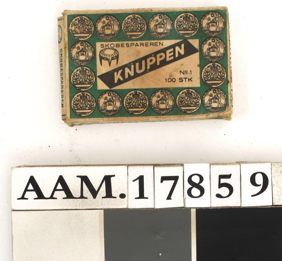 """En eske skobesparere """"Knuppen"""".  Ca. 1915.  Pappeske med sort tekst på hvit og grønn bunn: """"Skobespareren Knuppen no. 1  100 stk"""" med en rekke medaljer rundt fra utstillingen 1814-1914 i Christiania.  Merket """"norsk fabrikat"""" men uten firmaangivelse.  Lå i pengeskrin AAM.17858 fra banksjef Gjeruld Fløistad, antagelig fra huset Teaterplassen 1."""