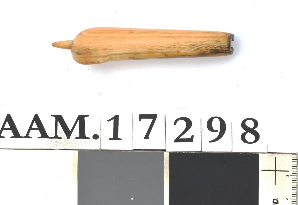Knivskaft med ruteformet tverrsnitt, avsmalnende mot bladet, som mangler. Skaftet ender i en fortykning til den ene side, med en spiss tapp ytterst.