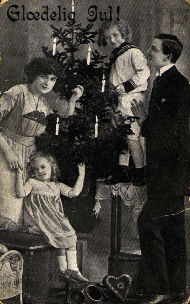 Julekort. Jule- og nyttårshilsen. Svart/hvitt. Interiør. Familie ved juletreet. Stemplet 23.12.1917.