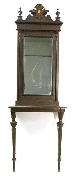 Konsollbord med to tynne, dreide ben, speil med utskåret kroneliknende figur og spir på hver side. Lakkert treramme.