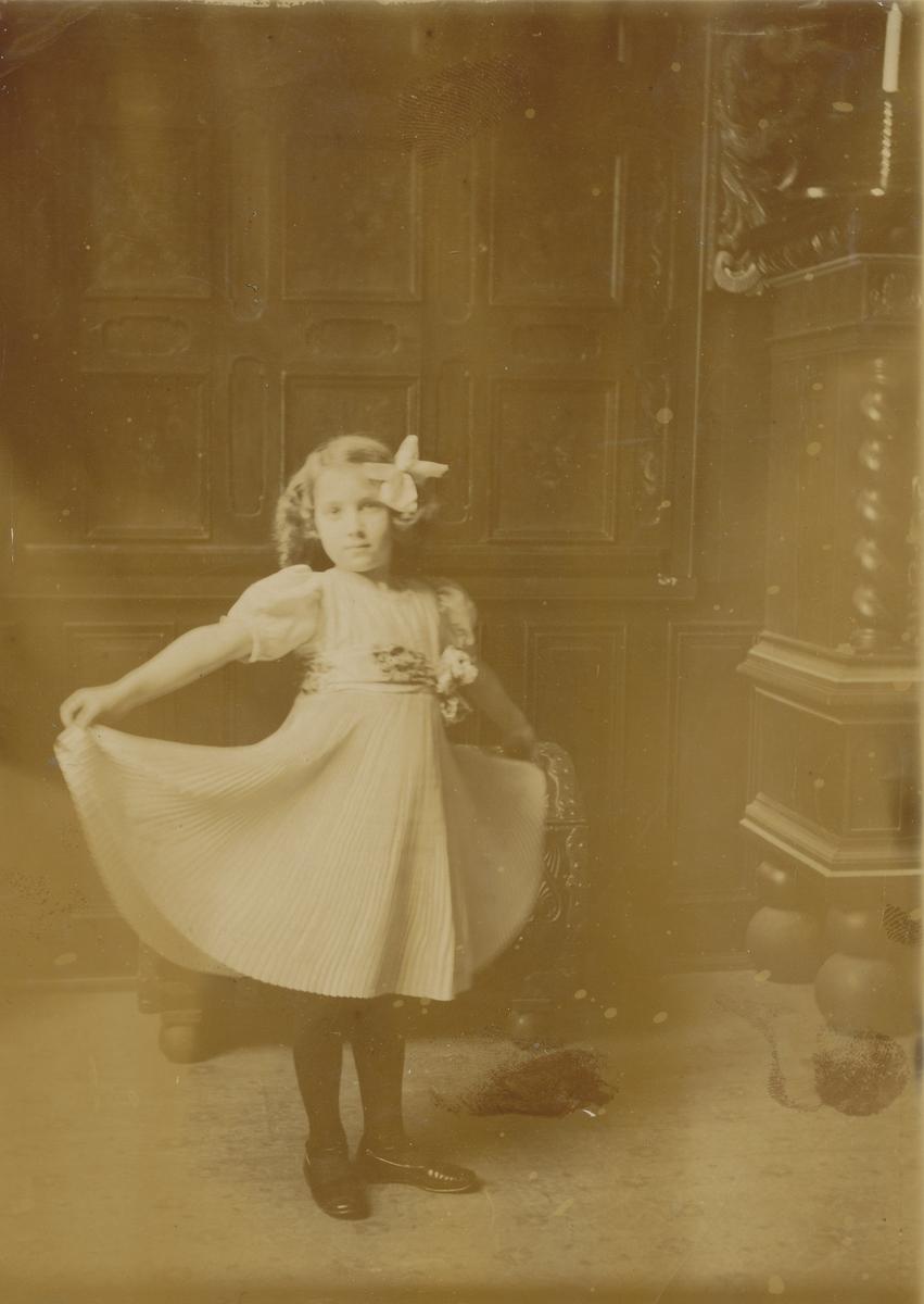 Pike i plissé-kjole, fotografert i atelieret i hovedhuset på Asker Museum.