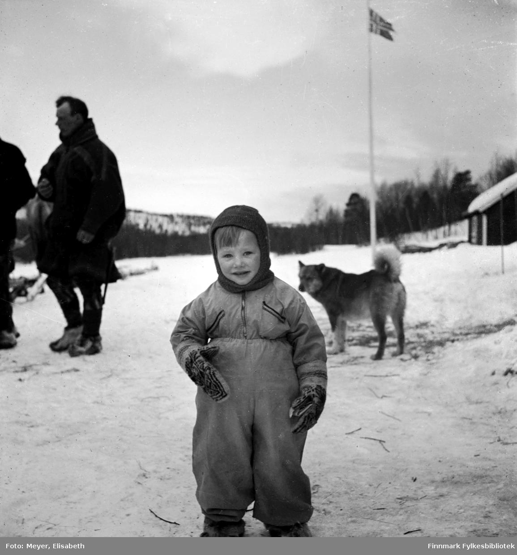 Arvid Dal fotografert i lek i snøen. Noen voksne til venstre i bakgrunnen.