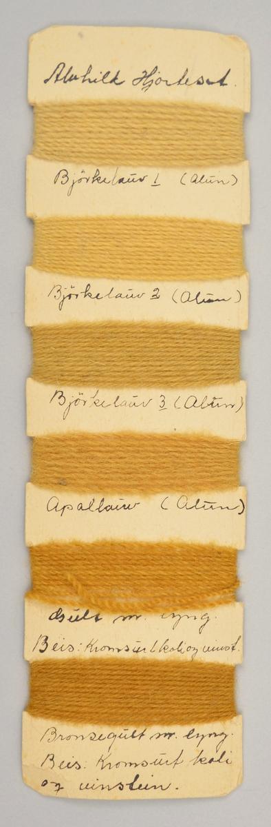 Pappbit der det er surra rundt ulltråd i ulike fargar i seks ulike felt. Her er fargane gul-brune. Under kvar farge står det skrive kva som er brukt for å lage fargen.