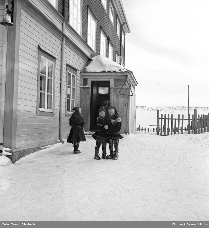 To skolegutter utenfor Kautokeino skoleinternat. Muligens en kvinnelig lærer til venstre i bildet. Skolen ble bygd i 1906. Påbygd i 1932 og ble brent i 1944.