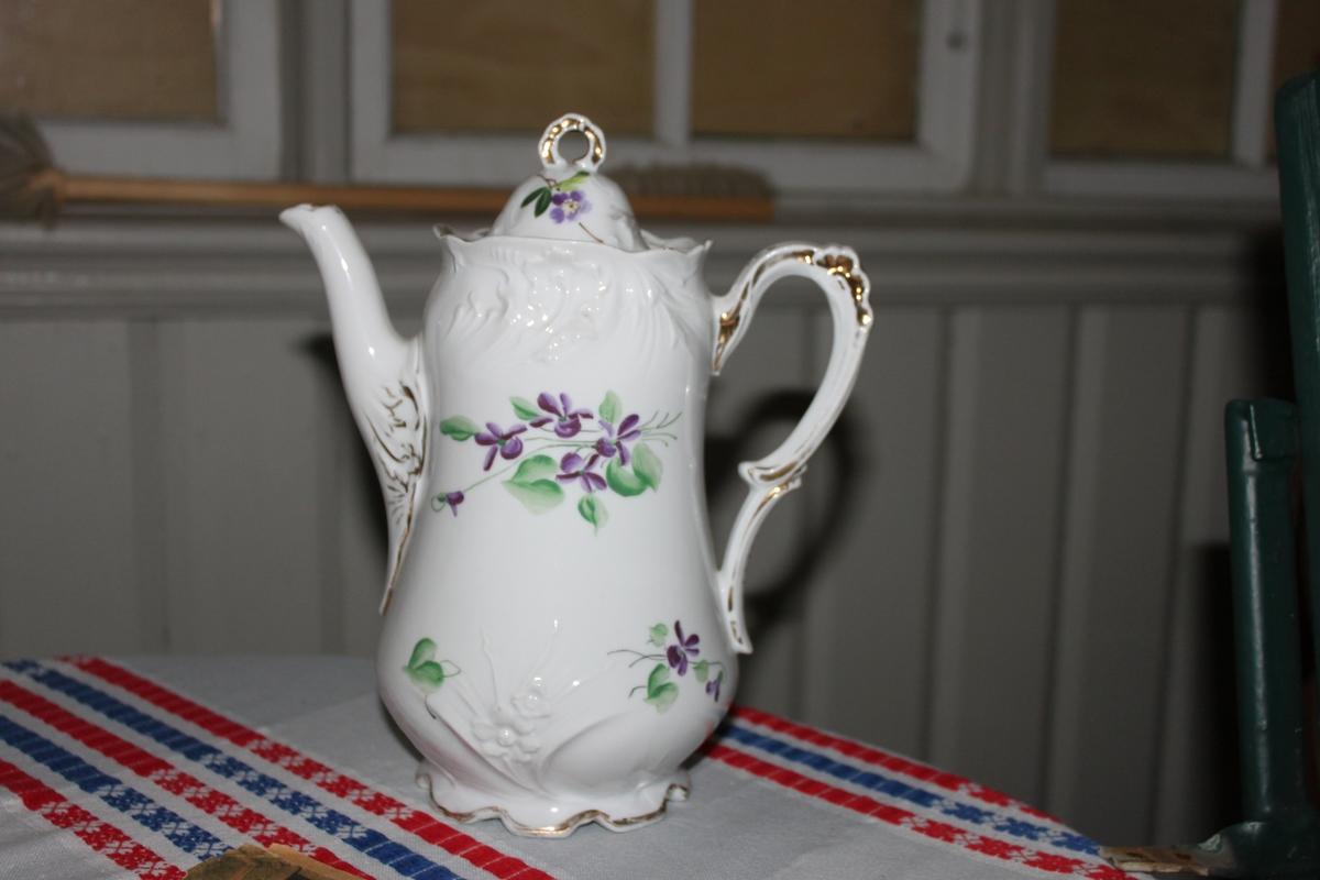 Kaffekanna trol. från 1940-talet. Vitt porslin med dekor av lila blommor och gröna blad. Förgyllda detaljer. Ett handtag på sidan. Lock med ett litet runt handtag. Dekor och påmålade blåsippor med gröna blad och bruna stjälkar.