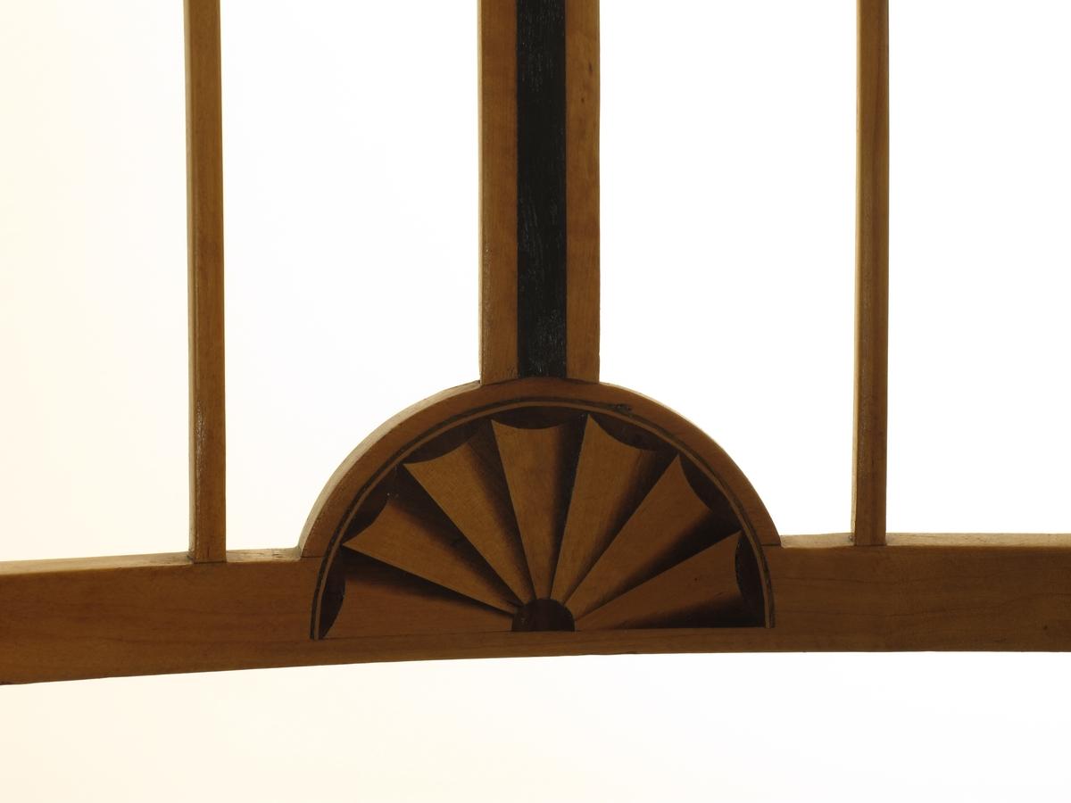 Gulbrun polert bjerk. Lett bakutbøyet rektangulær rygg, hvori midtbrett med innlagt stripe ibenholt, nederst vider midtbrettet seg ut til en halvsirkel hvori er innlagt en vifte av gul og brun bjerk. Midtbrettet flankeres i den åpne rygg av to smale spiler. Slanke, avsmalnende kvadratiske ben. Sargen svakt buet fremad i fronten. Stoppet, løs pute  på ramme skal ligge i setet (mangler).