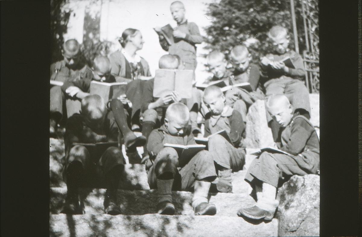 Gutter fra friluftsskolen Vangen har lesestund under smijernsportalen på Asker Museum sammen med Tilla Valstad og Gunhild Bakke (delvis skjult).