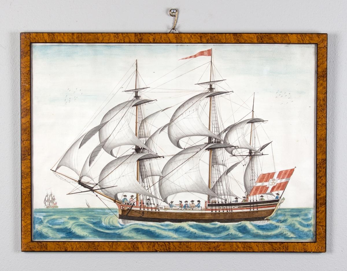 Fullrigger med full seilføring i rom sjø. Skipet sett fra langsiden. Dansk flagg med kongelig monogram i midten i akter, og rød vimpel i masten.