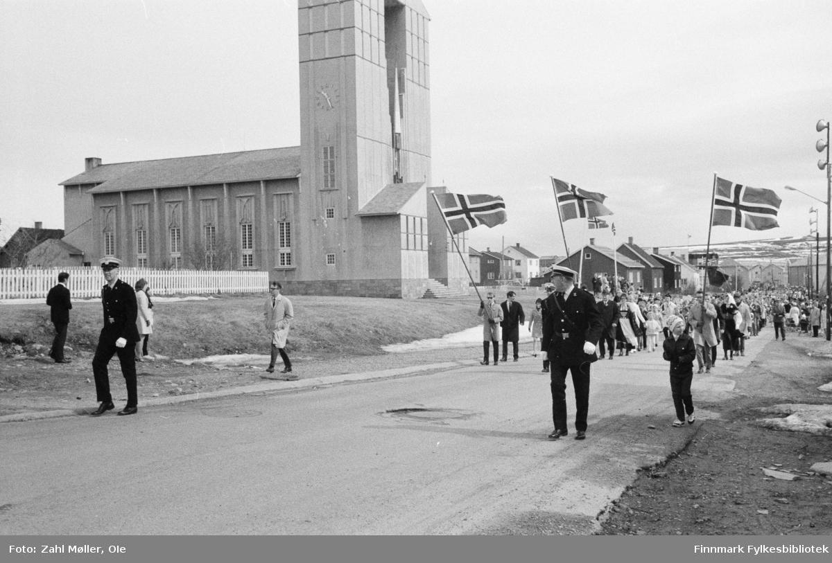 Vadsø, 17.mai 1970. Korpset spiller i gatene. Vadsø kirke i bakgrunnen. Politiet fremst i toget.