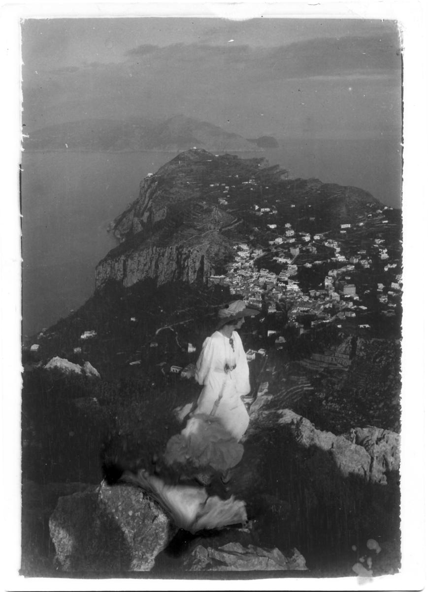 Ester Ellqvist-Bauer står på en klippa med utsikt över Capri i Italien.