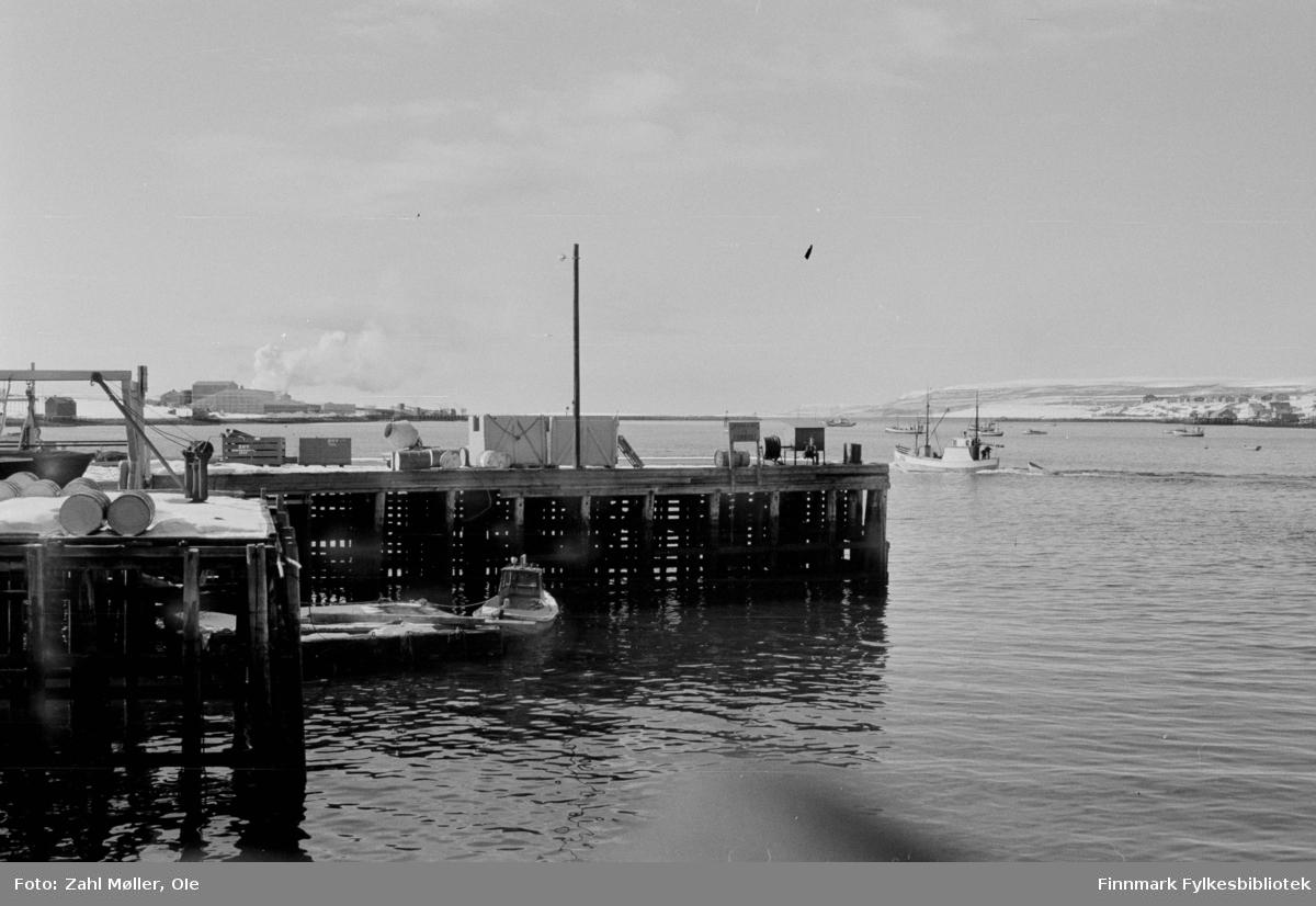 Fotoserie fra Vadsø, April 1968 fotografert av Vadsøfotografen Ole Zahl-Mölö. Havneområdet med kaianlegg. En fiskebåt er på vei ut fjorden og flere båter ligger i bakgrunnen ute i fjorden. Det stiger røyk opp fra Sildoljefabrikken på Vadsøya. En liten båt ligger fortøyd til kaia i front. På kaia sees tønner,  vinsjer og kasser.