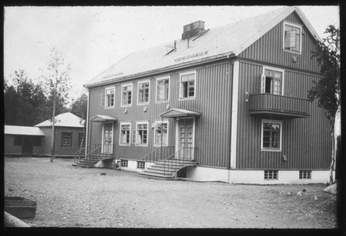 """""""187 b)"""" Sollia Barnehj., Sørvaranger"""" G.4"""" står det på glassplaten. Barnehjemmet i Sollia, Sør-Varanger. OGså  Bildet viser inngangspartiet og ene siden av bygget med en veranda i 2.etasje. Det er sommer og vinduene står åpne. Inngangspartiet har to separate innganger, med trapp opp til høy førsteetasje. Bygningen er bygget i tre og har en større og et par små piper på taket. På siden av huset står det en mindre bruksbygning. Bjørketrær med løv står på gårdsplassen som er gruslagt."""