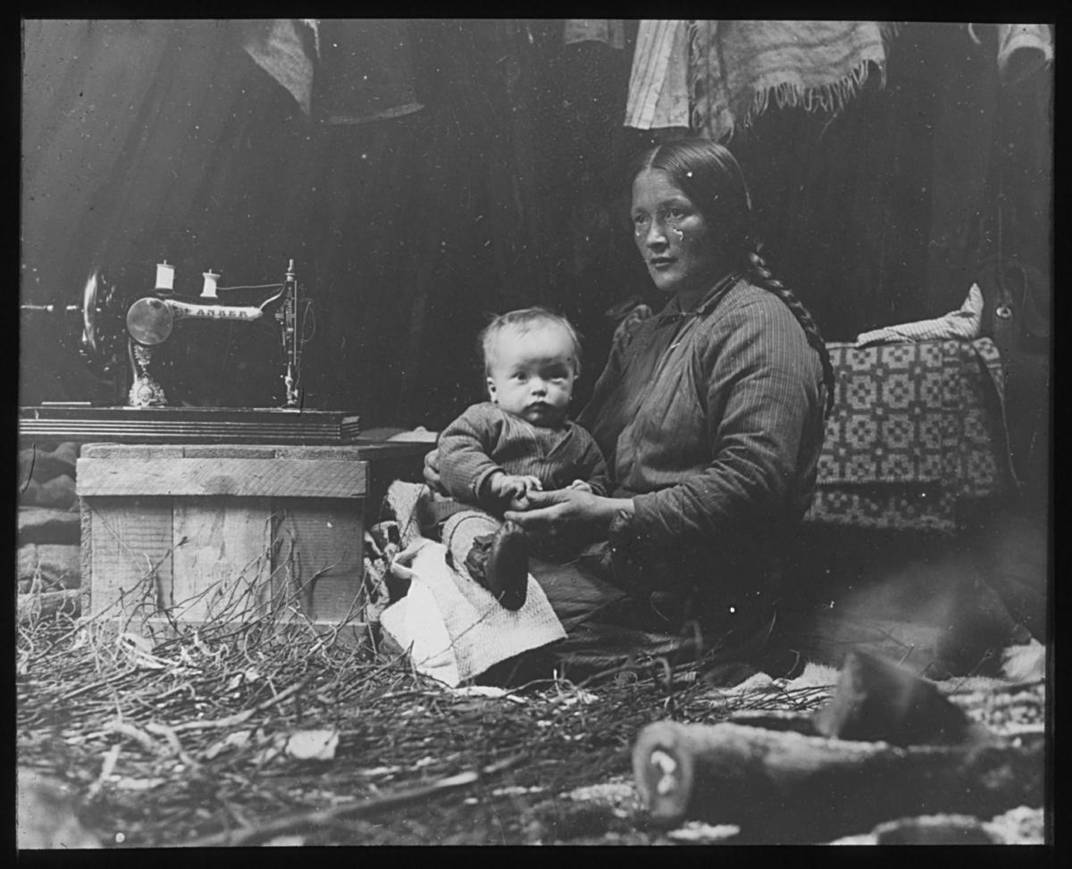 """""""Det indre av en koie."""" N.22 Portrett. Kvinne og barn. Kvinnen sitter på kne med barnet på fanget. Hun har håret flettet og begge har på seg varme klær, muligens samekofte. Barnet har håndsydde skinnsko på beina. Til venstre står det en symaskin på en trekasse. Det henger tepper og et sjal over kvinnen, og et vevd teppe ligger bak henne. Av veggen kan man anta at dette bildet er tatt inne i en gamme. Gulvet er dekket av bjørkekvister og det står en komse til høyre foran i bildet."""
