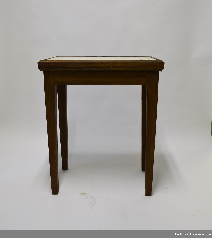 Lite bord, brunbeiset treverk. Bordplaten er opprinnelig en gravplate i marmor. Innskrift på undersiden. Et hjørne er sprukket.