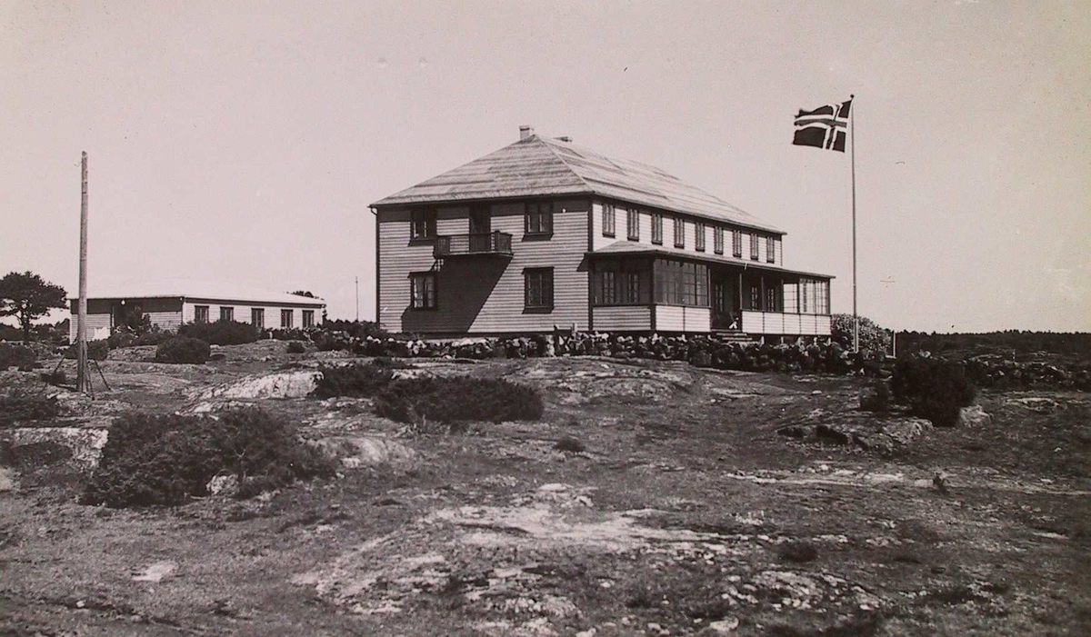 Breidablikk pensjonat på Tromøy, Stor toetasjes trebygning med liggende panel, valmet tak og veranda. Flagg t.h.