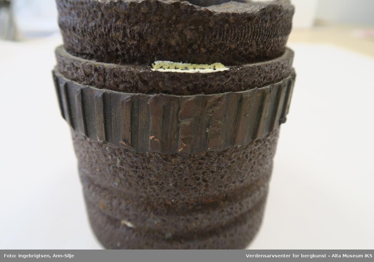 Bunnfragment av sprengt granat med rester etter styreband. Inn i fragmentet er det rester etter papp.