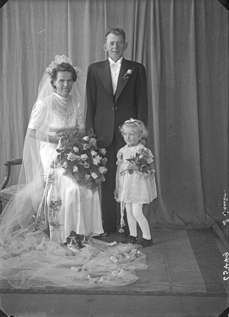 Portrett. Brudegruppe.  Brudepar og en blomsterpike. Bestillt av Karl J. Knutsen. Lillesundgt. 4.
