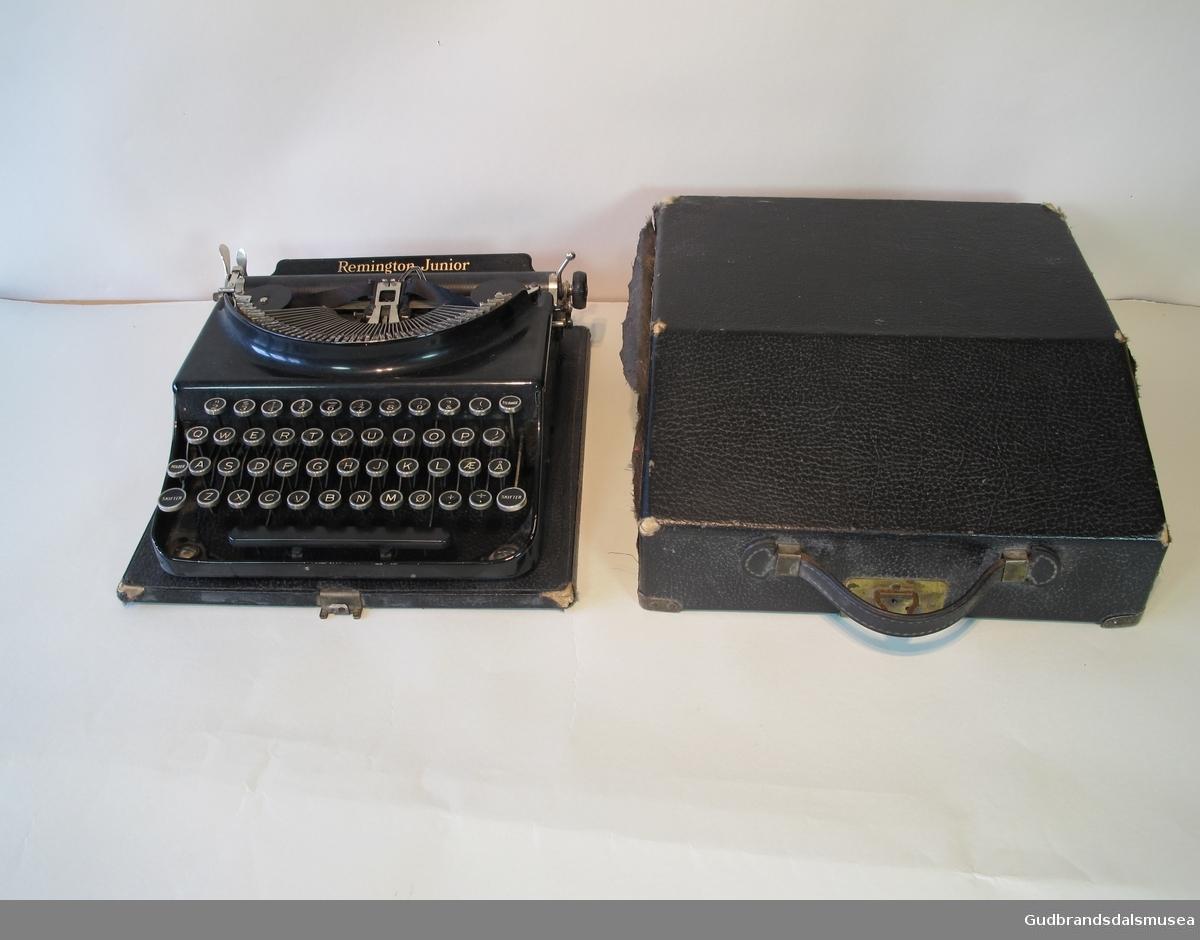 Manuell skrivemaskin med lokk. Har sort fargebånd. Norsk alfabet. Både maskin og lokk er noe slitt i kantene. Lokket har bærehåndtak.