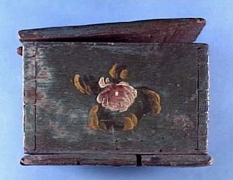 Blåmålat skrin med blomdekor samt märkning, låset saknas, färgen delvis bortnött på locket, sprucket i botten, har två fack, inköpt till museet för 4:-, spår av bläck inuti   Neg.nr: 1986-0012 Sakord: SKRIN Tillverkningstid: 1820 Material: ek järn mässing Teknik: målat sinkat spikat smitt Mått: L=305 B=185 H=130 Vikt: