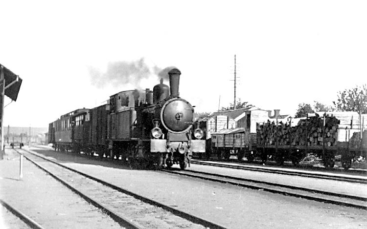 Bildtext: Skärvs socken. Valle härad. Västergötland. Axvall. Lok nr. 3 med vagnar på Axvalls järnvägsstation c:a 1920.
