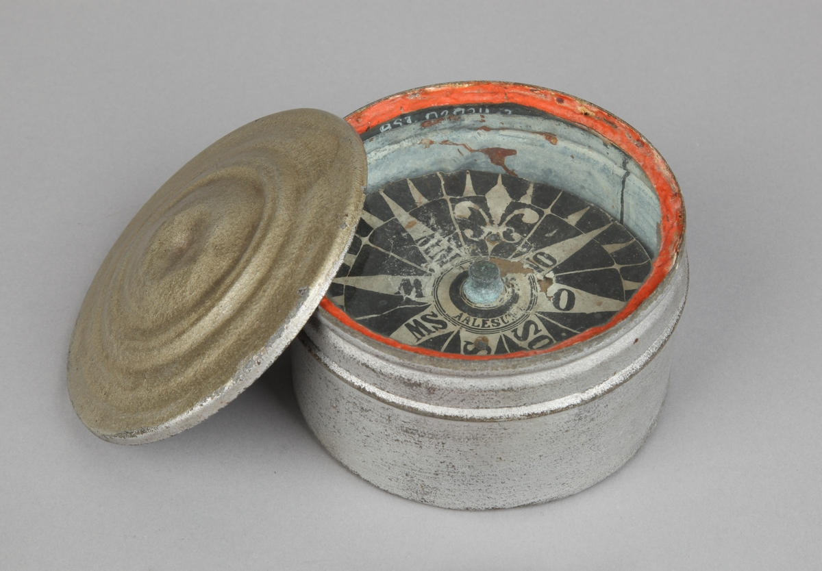 Rundt luftkompass i metallboks med lokk. Kompass-rose i papir.