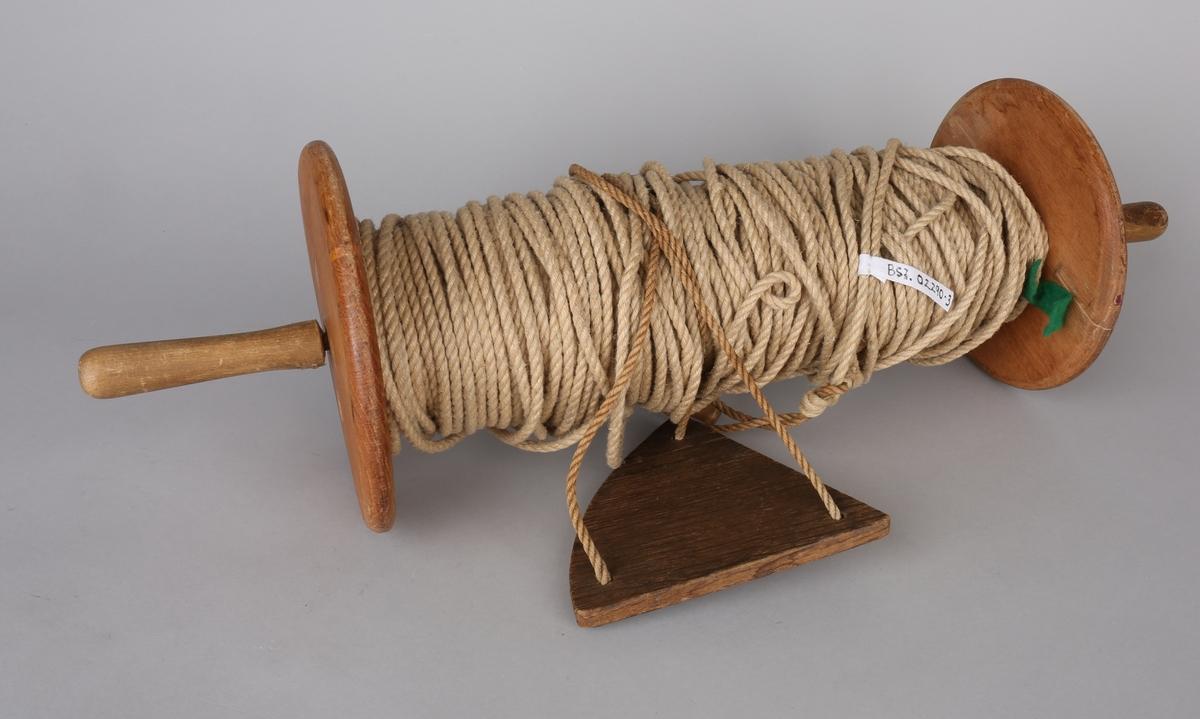 Loggline på rull med  flyndre. Trerull med hampetau som kan holdes og snurres med håndtak på hver side.