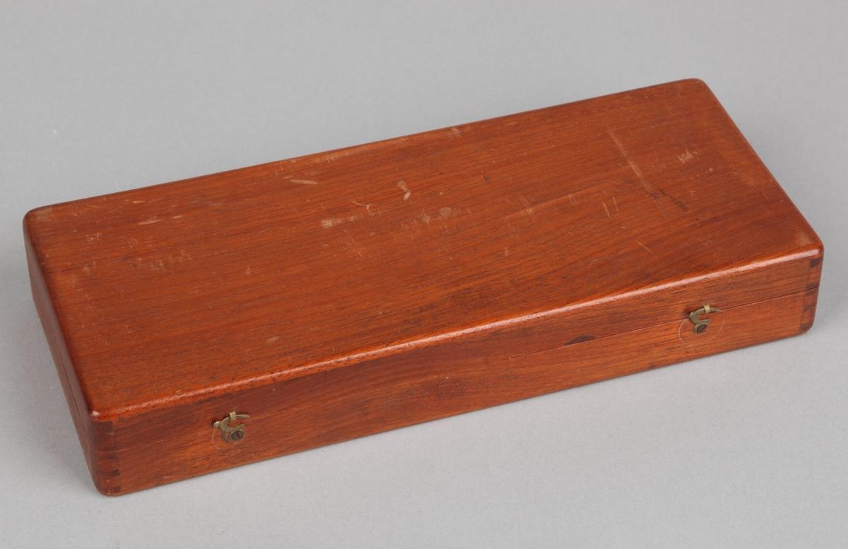 Kornvvekt i rektangulært mahognyskrin. Inne i skrinet enda et lite rektangulært skrin med vektdeler.