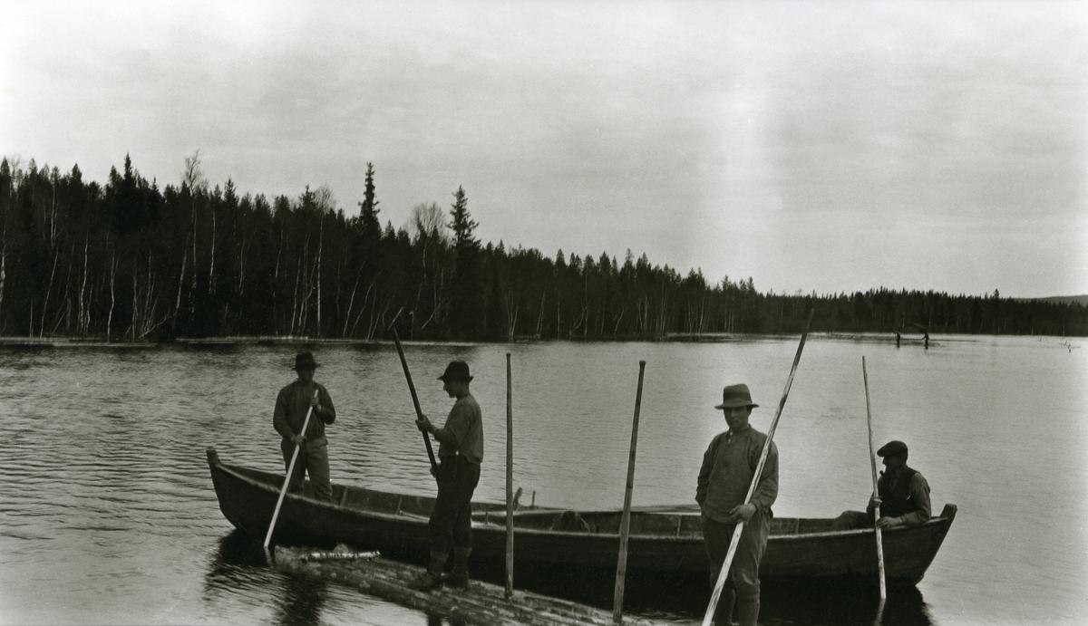 """To menn i båt og to menn på tømmerflåte; fløtere; i en dam ved Grøna """"Breidfloa"""" øst for Galåsen.  Fra venstre: 1) Kristian Haugset (16/4 1889 - 1978), 2) Johan O. Flermoen (Akerhaug) (22/11 1883 - 1969), 3) Kristian Christiansen, Rønningen, Vestby (22/2 1900 - 1975), 4) Emil Tannåneset (26/8 1877 - 1960)."""