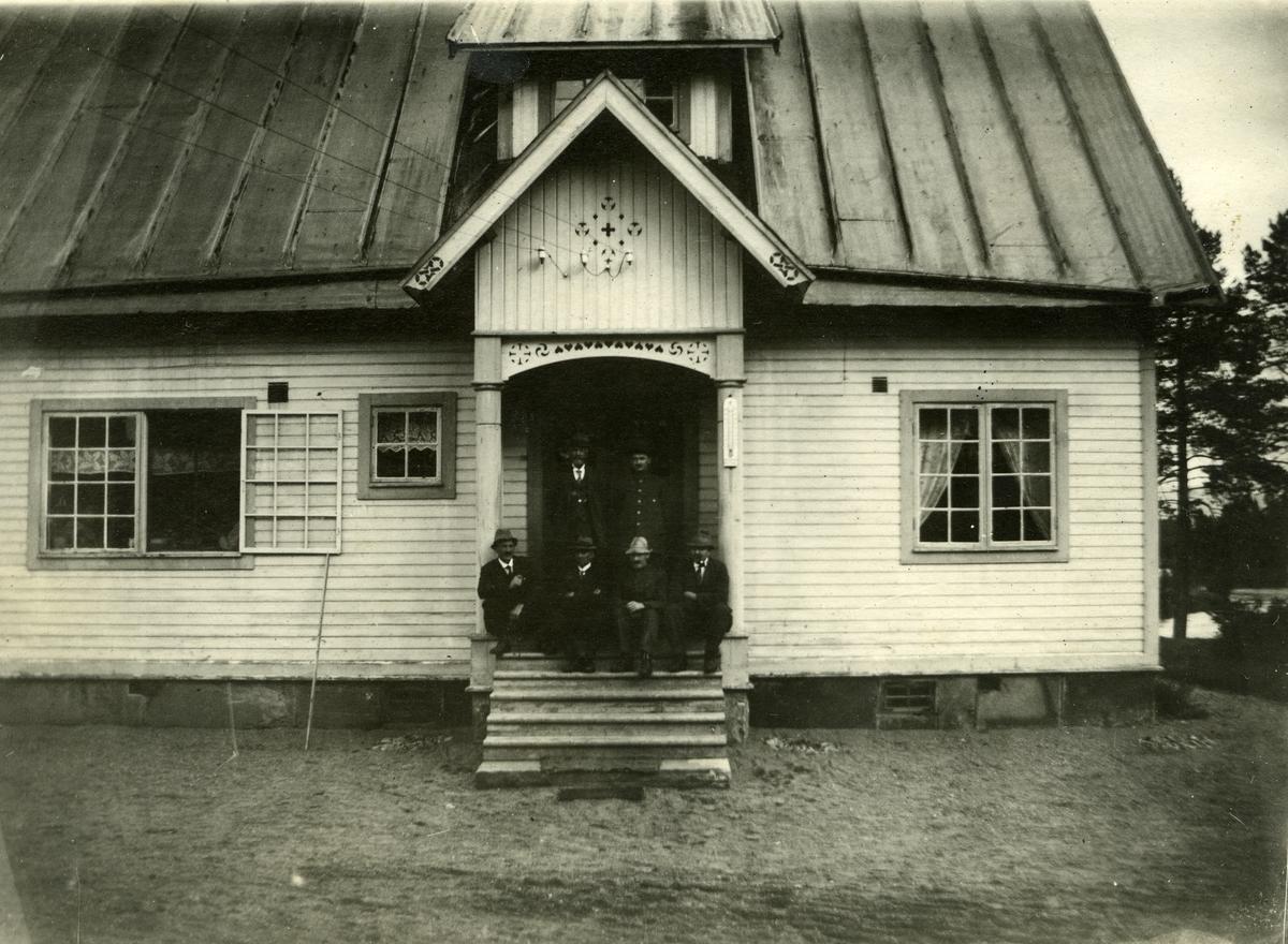 Våningshus i Adolfsnes, Ljørdalen. Fire menn sittende på trappa, to menn stående bak.