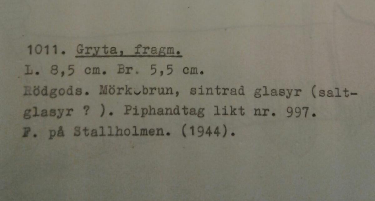 Kermikhandtag av yngre rödgods som utgör ett fragment av en låg panna eller en mindre trefotsgryta. Mörkbrun sintrad glasyr  på kärlbukens insida. Handtaget är ihåligt med en bred öppning i änden och avslutas med en utkragad kant. Typ B, år 1425 - 1550. Tillverkad i södra Skandinavien.