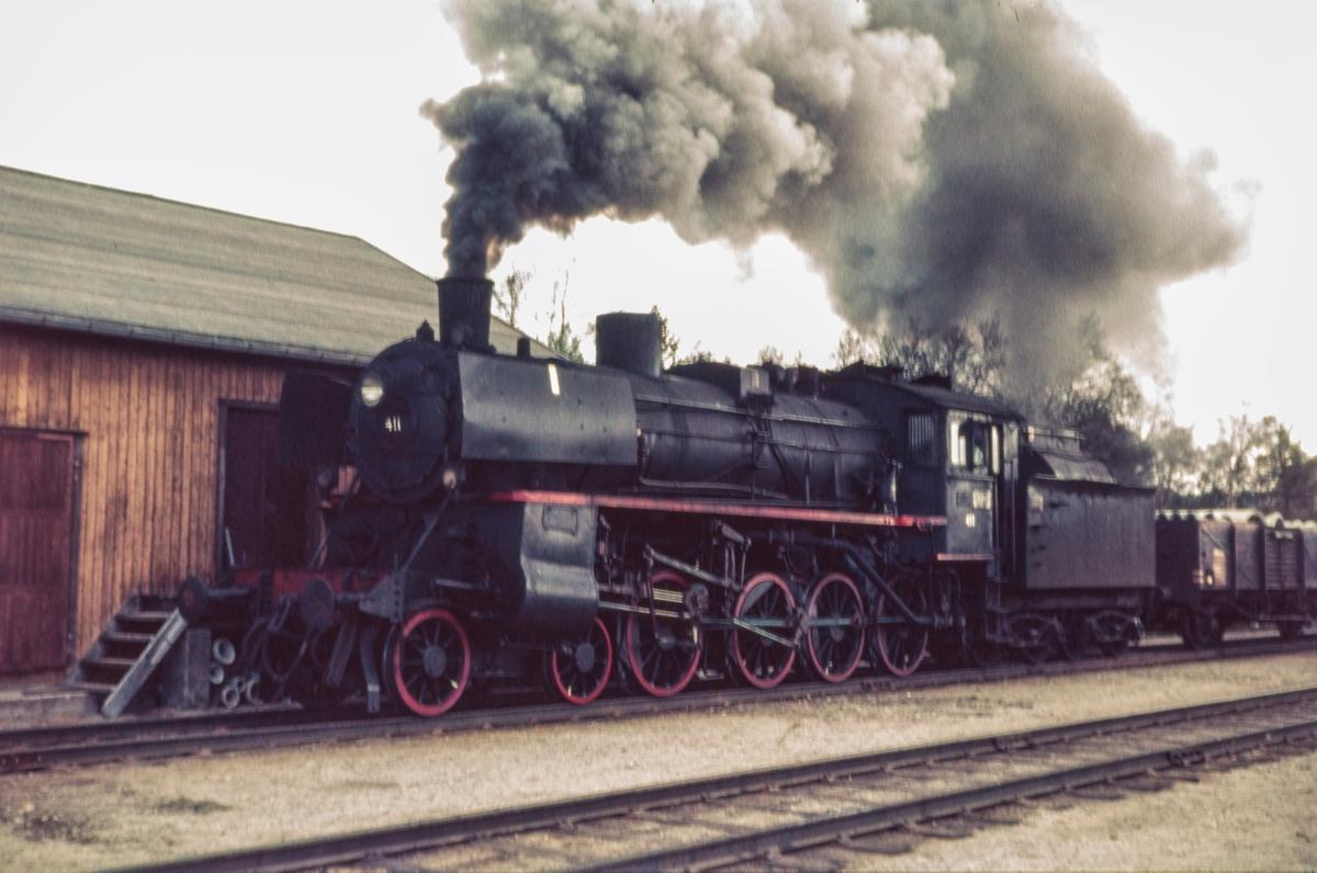 Damplokomotiv type 26c nr. 411 med nordgående godstog på Røros stasjon.