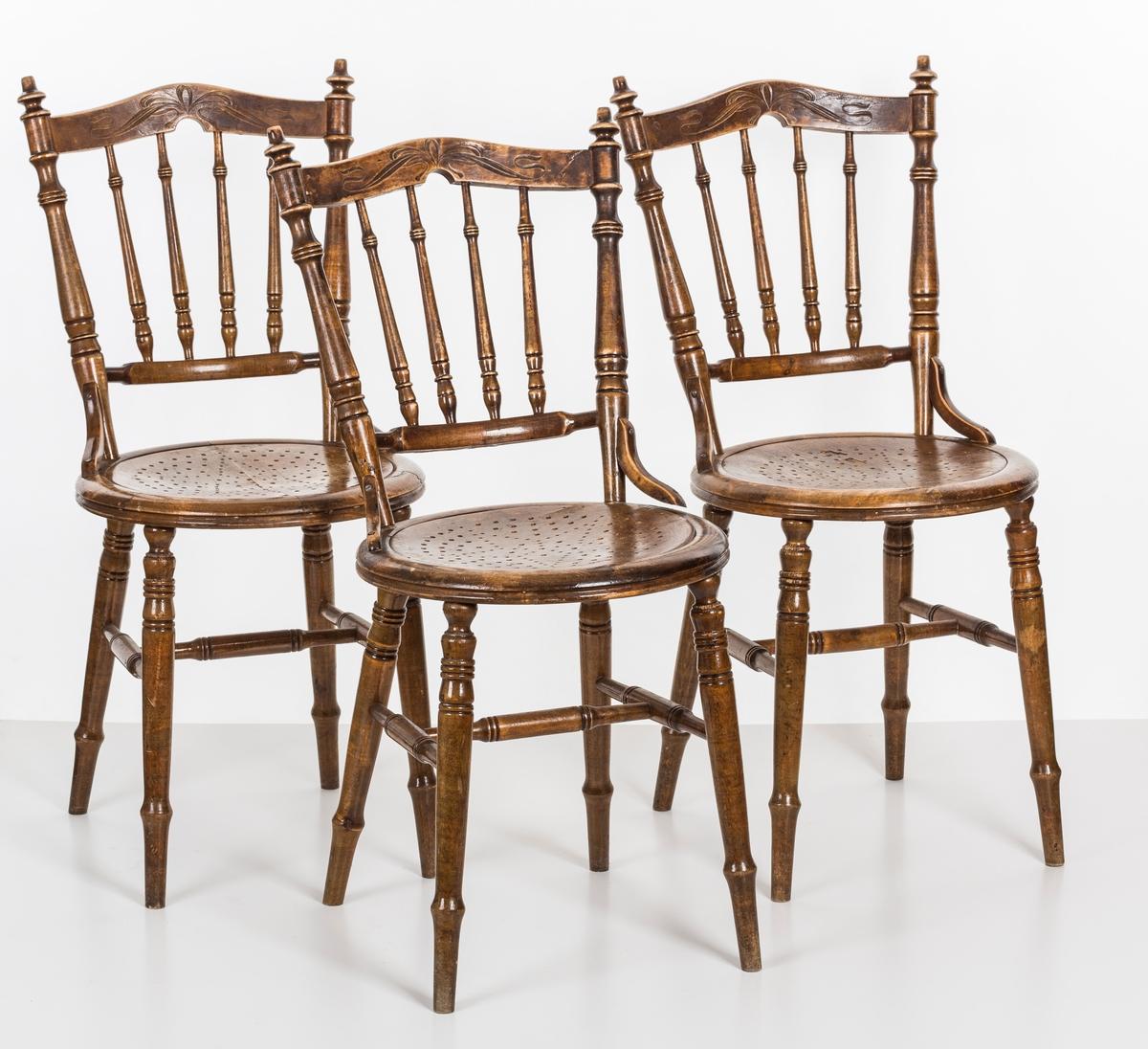 Stol i lakket treverk. Rundt stolsete med hullemønster. Rygg som er svakt buet med spiler og mønster. Dreide ben og spiler i rygg.