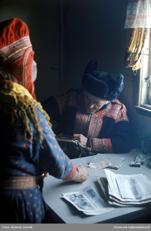 """Postfører Mathis Mathisen Buljo, bedre kjent som """"Post-Mathis"""" i samiske kretser, besøker en av sine postkunder på postruta. Her holder Mathis på med en innbetaling eller utbetaling til postkunden.  Fotograf Henrik Ørsteds bilder er tatt langs den 30 mil lange postruta som strakk seg fra Mieronjavre poståpneri til Náhpolsáiva, videre til Bavtajohka, innover til øvre Anárjohka nasjonalpark som grenser til Finland – og ruta dekket nærmere 30 reindriftsenheter. Ørsted fulgte «Post-Mathis», Mathis Mathisen Buljo som dekket et imponerende område med omtrent 30.000 dyr og reingjetere som stadig var ute i terrenget og i forflytning. Dette var landets lengste postrute og postlevering under krevende vær- og føreforhold var beregnet til 2 dager. Bildene gir et unikt innblikk i samisk reindriftskultur på 1970-tallet. Fotograf Henrik Ørsted har donert ca. 1800 negativer og lysbilder til Finnmark Fylkesbibliotek i 2010."""