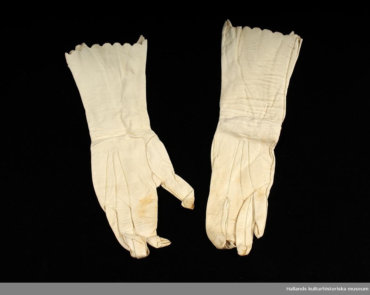 """A 1+2 : Kvinnohandskar i vitt skinn med knappar på insidan av handleden. Linjer från skräddarens uppmätning finns kvar på insidan av handskarna. Mönsterklippt kant i handskens mynning. Knappar av pärlemor. B 1+2 : Fint stickade brudstrumpor med mönsterstickad kant över foten och röd rand vid strumpans mynning. På B2 finns ett broderat """"v"""" (vänster) C: Brudskor i siden med två rosetter över foten. Skon är sydd. Sulan i läder. Str 36/4."""