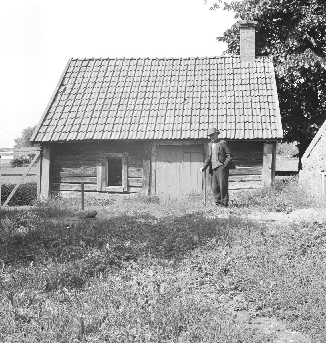 Motiv från Egeby källgård i Västerlösa. Dokumentation av Östergötlands museum 1940. Mannen är gårdens ägare vid tiden, Hjalmar Andersson.