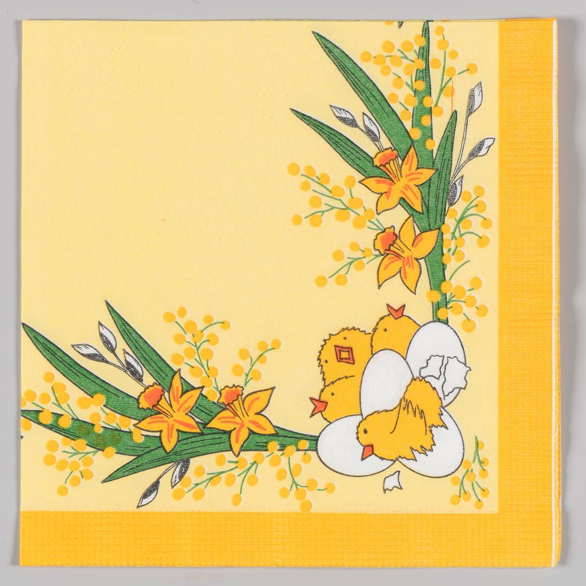 """En kylling som sitter i skallet til et egg, flere hvite egg og tre pippende kyllinger. Buketter med påskeliljer, grener med """"gåsunger"""" og gule mimoser."""