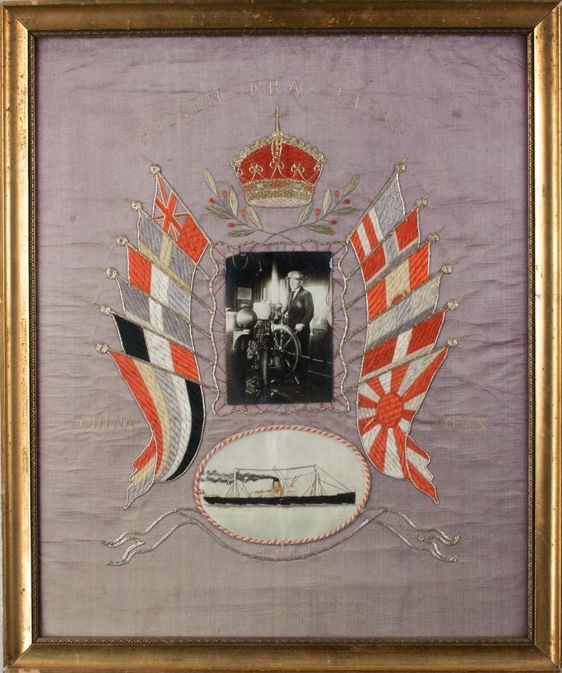 Brodert silkebilde av DS ERLE i stående format. Midt i motivet fotografi av sjømann til rors, omkranset av seks ulike flagg på hver side og krone øverst. Under et brodert bilde av DS ERLE.