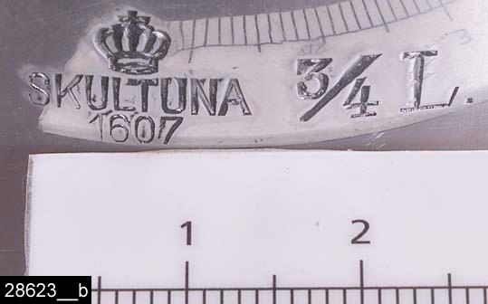 """Anmärkningar: Kastrull, 1930/40-tal.  Rund kastrull med ett handtag med en genombruten dekor längst ut. Till höger om handtaget finns stämplar i form av en krona samt texten """"SKULTUNA 1607 3/4L"""" (bild 28623__b). På handtaget hänger en lapp med texten """"SKULTUNA BRUK GRUNDLAGT ÅR 1607"""". Föremålet har ej återfunnits i några kataloger från Skultuna. Snarlika kastruller finns avbildade under 1930-40-talen. Möjligen är kastrullen ett fel i produktionen, den är märkt 3/4L men rymmer ca 1,5L. Enligt en broschyr, utgiven av museet 2007 och benämnd """"Skultunastämplar 1800-2000"""", började den typ av stämpel som finns på föremålet användas 1922. Den användes fortfarande år 2007. H:120 D:145 Br:290 (avser måttet diameter samt handtagets mått)  Tillstånd: Små märken i botten.  Historik: Gåva från SAPA AB, Division Service, 2002. Föremålet stod i ett skyddsrum på bruksområdet i Skultuna."""