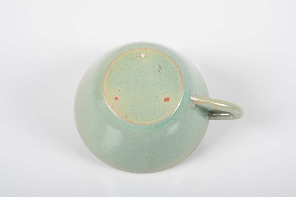 Rund kopp i keramikk med grønn lasur. Buet hank. To små knotter (mangler en tredje knott) på undersiden av koppen, usikker funksjon.