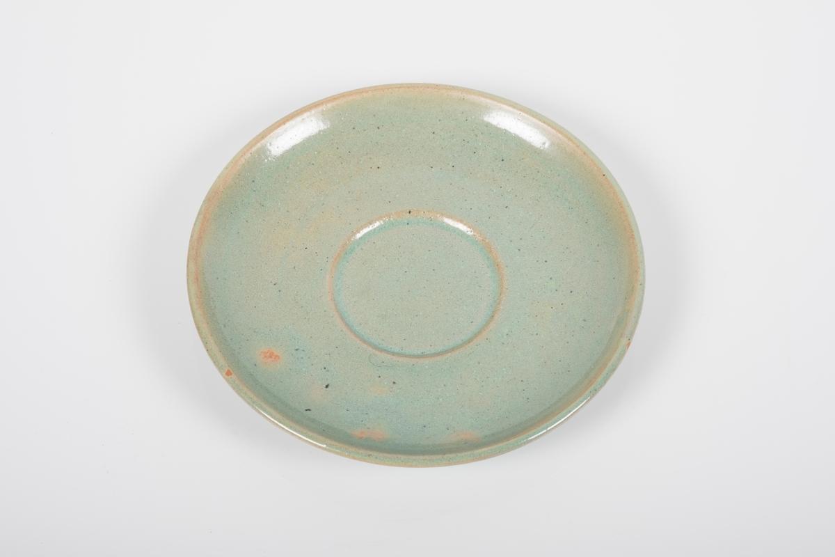 Skål i keramikk med grønn lasur. Skålen har spor etter tre knotter på bunnen, usikker funksjon. Bunnen har matt overflate.