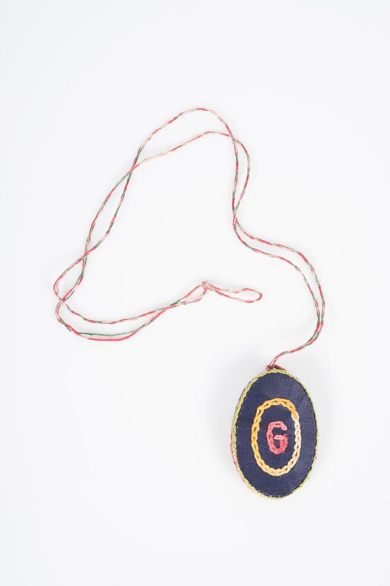 Håndsydd medaljong i tekstil. På forsiden er det brodert ei rosa blomst på brunt stoff. Kanten er brodert med gul tråd. På baksiden er det brodert en rød G inn i en gul oval på mørkeblått stoff. Kanten er brodert med grønn tråd. Innsiden er foret med lyseblått over og svart stoff under der bildet skulle være. Innerkanten er brodert med rød tråd. Motsatt side er foret med mørkeblått stoff, og kanten er brodert med lilla tråd.