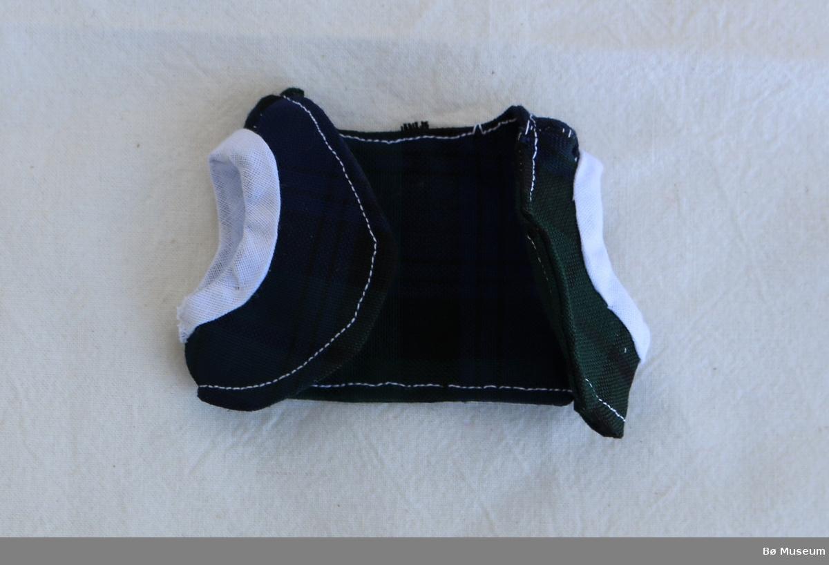 Dokkekjole (a) med rynkeskjørt, påsydde skulderstropper og to krykknapper i ryggen. Sømmen har delvis gått opp mellom skjørt og liv bak. Fall nede på skjørtet er sydd med sikksakksøm. Vesten (b) er kort og i rutete stoff og med kvit kant rundt erma.