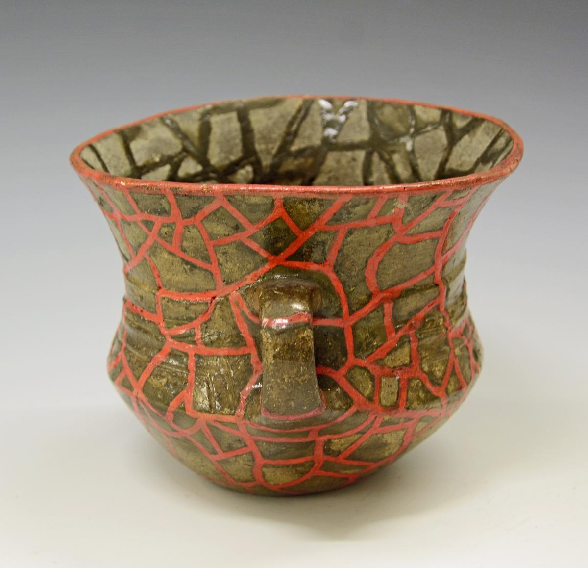 Sterkt restaurert leirkar, med hank på siden, av form som Bøe: Jernalderens keramikk, fig. 73 (se også fig. 113), med lavbuket nederdel, høy, jevnt svinget skulder og hals, således at randen er svinget ut til større bredde enn buken. Hanken er rund, uornert. I halssvekket løper en dyp hulkile, litt nedenfor den er en skråriflet ribbe. det smale nedre felt av skulderen er dekorert med avbrutte hulkiler av form som langstrakte trapeser, uten nedre linje, denne dannes av bukovergangen. Inni hver av disse felter er det to små fordypninger. Godset er ganske tynt, som det synes jevnt glattet, fargen er mørk, men den sterke restaurering som karet har vært utsatt for, kan ha forårsaket mye. Ingen funnopplysninger Datering: overgangen romertid-folkevandringstid, sannsynligvis begynnelsen av 5. årh.